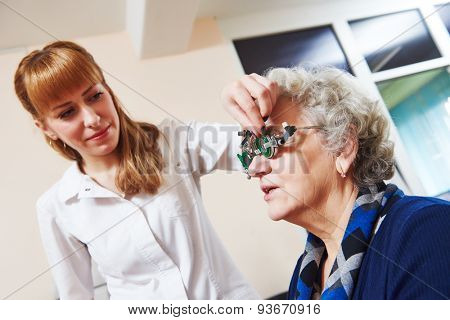 Optometry. female doctor ophthalmologist or optometrist examines senior woman eye sight with phoropter in clinic
