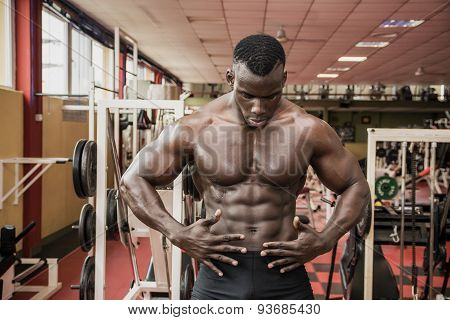 Attractive hunky black male bodybuilder in gym