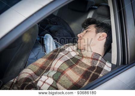 Young handosme man sleeping in his car