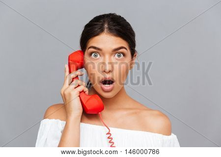 Close up portrait of amazed beautiful woman talking on the phone tube isolated on a gray background