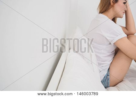 sad woman sitting on white the bed at bedroom. copy space in left.