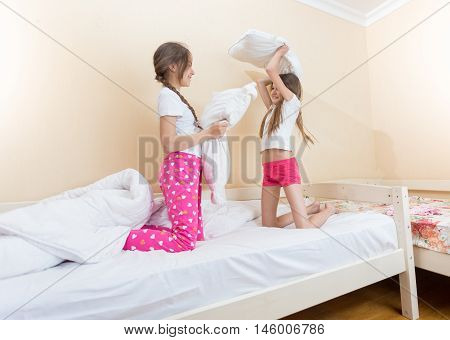 Two happy girls fighting with pillows at bedroom