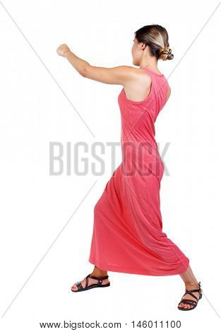 skinny woman funny fights waving his arms and legs. slender woman in a long red dress punches.