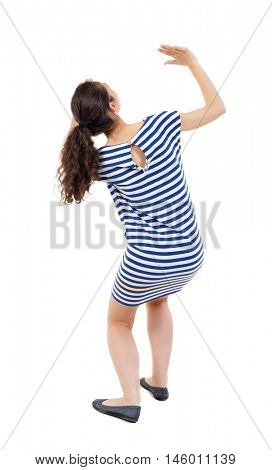 back view of woman protects hands from what is falling from above. Swarthy girl in a checkered dress frightened of something on top.