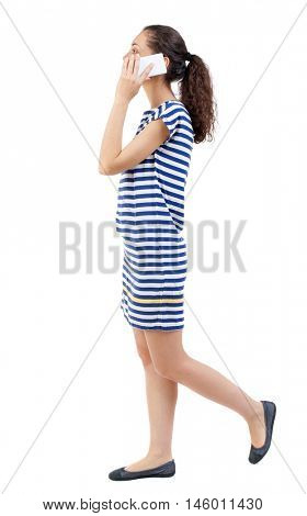side view of a woman walking with a mobile phone. Swarthy girl in a checkered dress is talking and white smartphone.