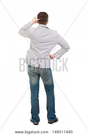 Back view of man . guy in a gray jacket thoughtfully scratches his head.