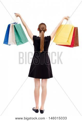back view of woman with shopping bags. Isolated over white background. Blonde in a short black dress holding aloft shopping bags.