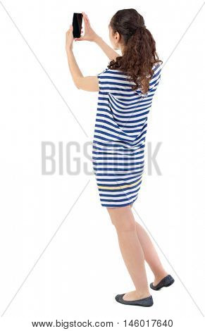 back view of standing young beautiful woman using a mobile phone. girl watching. Swarthy girl in a checkered dress takes on the phone.