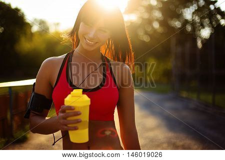 healthy fitness girl with protein shake. Smile sport woman in the sunny day