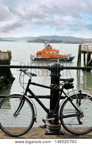 rescue lifeboat in cobh harbour county cork ireland with bicycle in foreground chained to post