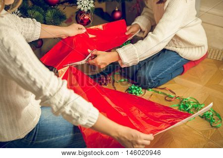 Closeup toned image of girl cutting red wrapping paper for Christmas presents