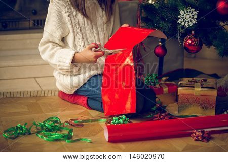 Closeup toned image of girl sitting under Christmas tree and cutting wrapping paper