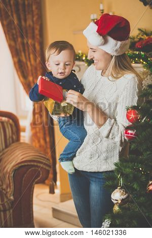 Toned portrait of happy young mother giving Christmas present to her cute baby boy at living room
