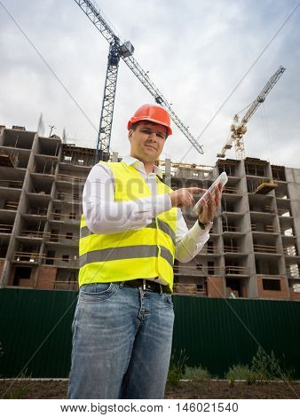 Portrait of smiling construction engineer posing with digital tablet