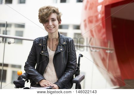 Smiling disabled female university student on mezzanine