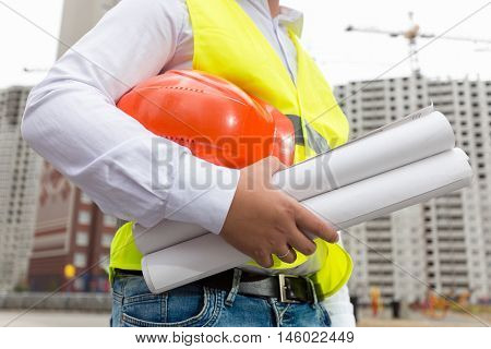 Closeup image of construction engineer holding blueprints and orange hardhat at building site