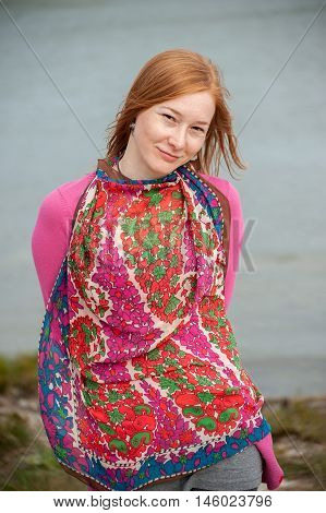 Outdoor portrait of a beautiful redhead woman with scarf