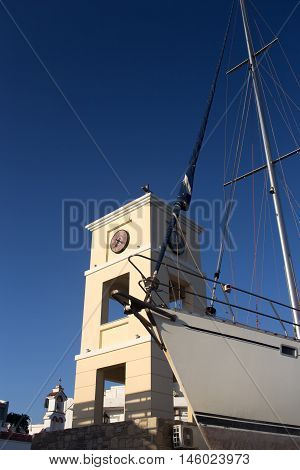 Prow of a sailing boat and a chapel on a background of blue sky