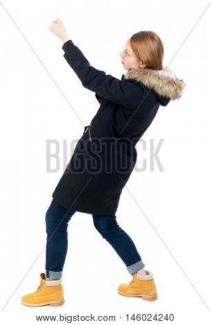 Side view. girl in winter jacket pulls his hands on top of the rope Standing young girl in parka. girl in warm winter jacket is a black side and pull the rope from above.