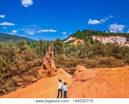 Two boys of seven and four years admired the magnificent nature. Languedoc - Roussillon, Provence, France. Orange and red picturesque hills