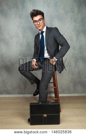 happy young business man sitting near brief case , in studio
