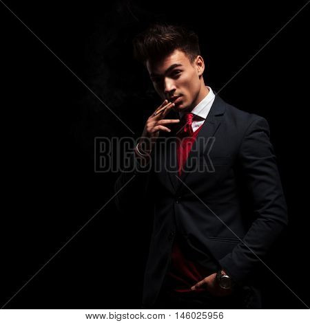 arrogant elegant young man smoking his cigarette on black background