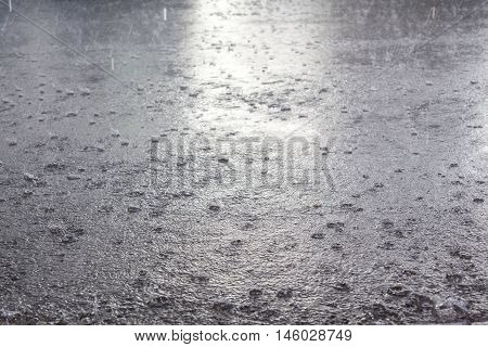 Rainy day background. Rain drops falling in the flood.