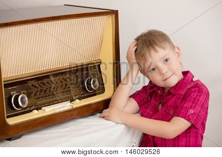 Retro style, surrounded by old things fifties of the last century. Cute little blond boy in red shirt is posing near the old radio.