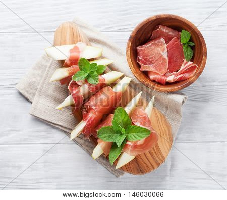 Fresh melon with prosciutto and mint. Antipasti. Top view on wooden table