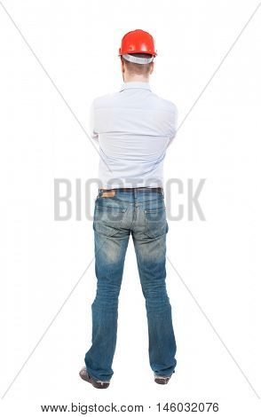 Backview of an engineer in construction helmet stands. Standing young guy. Rear view people collection.  backside view of person.  Isolated over white background. Engineer crossed his arms and watches