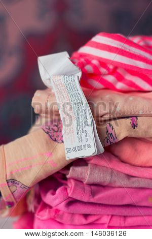 Pile of colorful clothing prepared for washing washing label visible