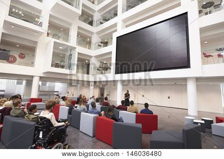 Students at a lecture in the atrium of a modern university