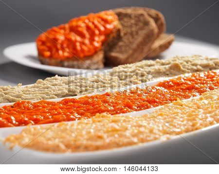 Three types of dips - mayonnaise tomato dip and eggplant dip. Close up bread slices on background