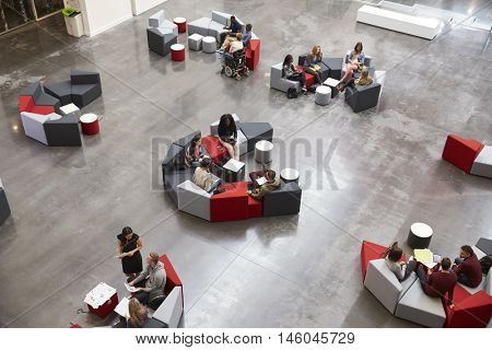 Students sit in groups in a modern university atrium