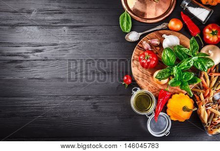 Vegetables and spices ingredient for cooking italian food on black wooden old board in rustic style