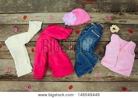 Children's clothing and accessories: jeans, jacket, hat, hair clips and warm vest on old wooden background. Top view.