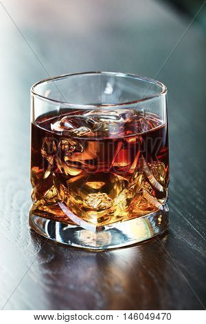 Whiskey on the rocks on a table. Shallow depth of field.