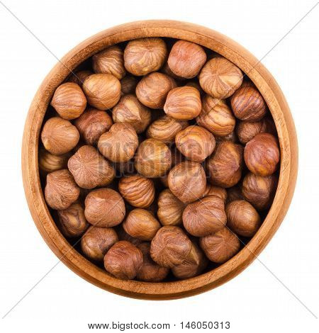 Hazelnuts in a wooden bowl on white background. Shelled ripe seeds of a cultivated Corylus species. Edible raw fruits. Isolated macro food photo close up from above.