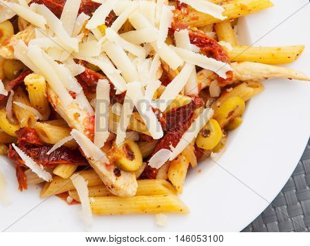 Pasta with chicken dried tomatoes and parmesan cheese. Close up
