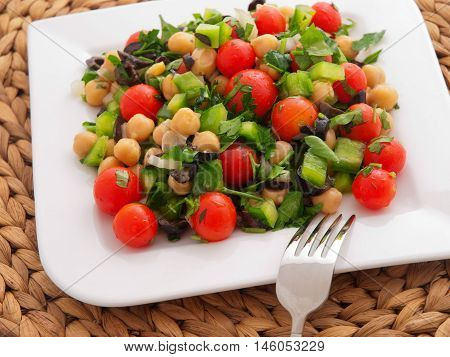 Salad with tomatoes cucumbers and chickpeas. Horizontal shot