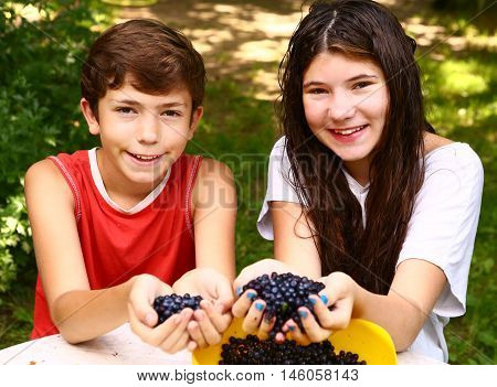 teenager siblings brother and sister with handful of bilberries close up smiling portrain on the green grass summer background