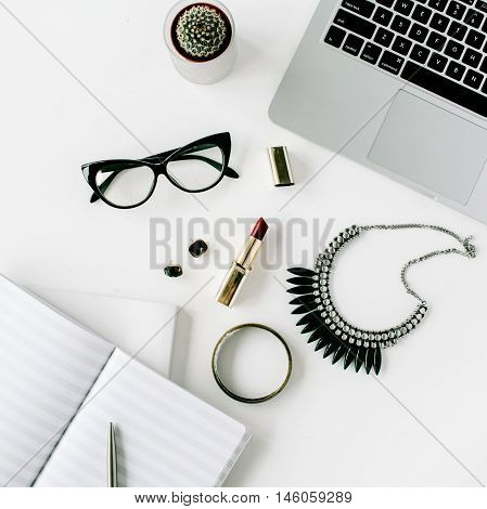 Flat lay top view office desk. Workspace with laptop feminine accessories glasses cactus diary lipstick necklace on white background.