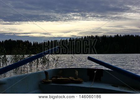 watching the sunset on the lake with boat, soft rippling water, a beautiful sky with clouds, coniferous forest on the horizon, the karma of the boat, the oars, on the bench of the boat visible mushrooms