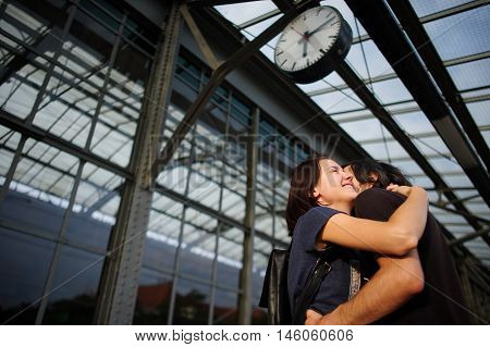 Loving couple met or parted on the platform under the clock. The young man put his arm around the girl. Girl smiling happily.