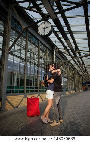 Loving couple met or parted on an empty platform under the clock. The young man put his arm around the girl. They tenderly looking at each other.