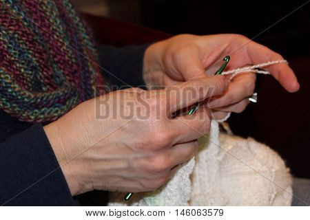 Closeup on hands crocheting with white yarn