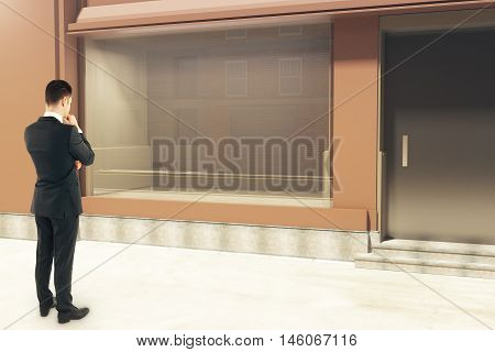 Thoughtful businessman looking at empty clean storefront in daylight. Side view Mock up 3D Rendering