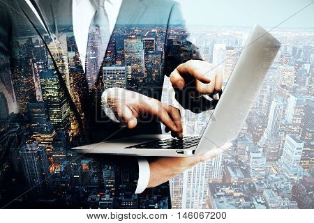 Closeup of two businessmen's hands using laptop on city background. Double exposure