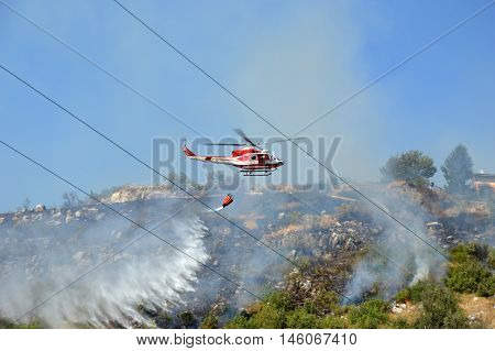 August 21 2016-Monti Prenestini-Castel San Peter- Roma-Lazio-Italy-the helicopter of the fire brigade to put out an arson attack on the slopes Prenestini who is skirting the first inhabited houses