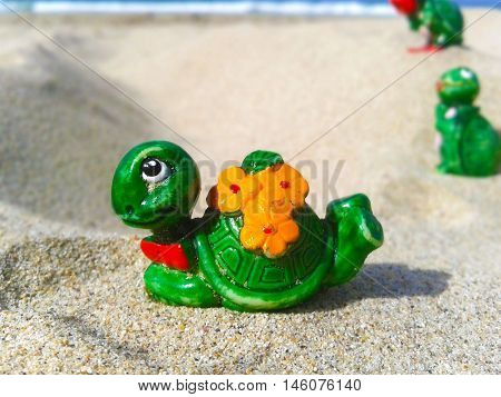 Nueva Esparta, Venezuela 07 september 2016. A little toy of a lady turtle with other turtles back on the beach sand